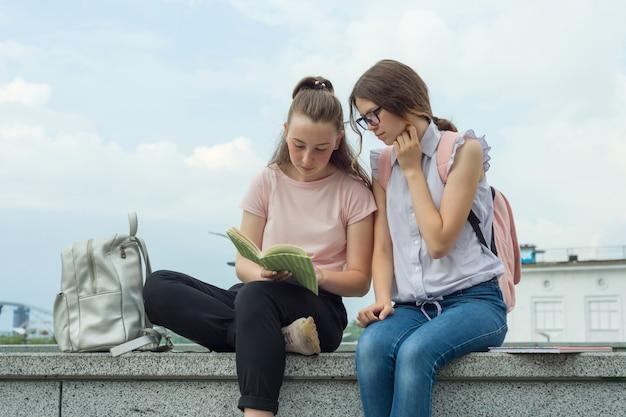 Dois, meninas aprendendo, estudantes, com, mochilas