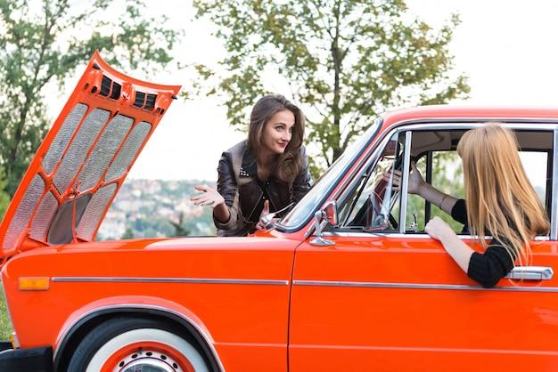 Dois, meninas jovens, com, um, carro quebrado, estrada