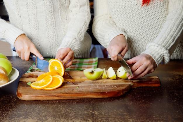 Dois, meninas jovens, cozinha falando, e, comer, fruta, estilo vida saudável, close-up