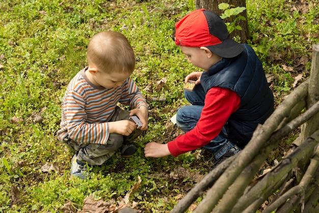 Dois meninos acendendo uma pequena fogueira