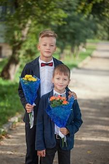 Dois meninos adoráveis com um lindo buquê de flores na natureza