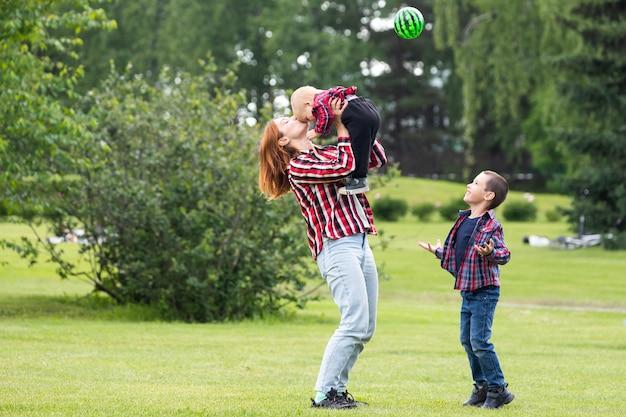 Dois meninos alegres bonitos irmão criança com mãe brincar ao ar livre no parque.