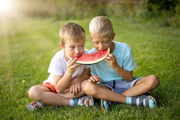 Dois meninos alegres e felizes comem melancia em uma clareira verde com sua comida saudável e ensolarada