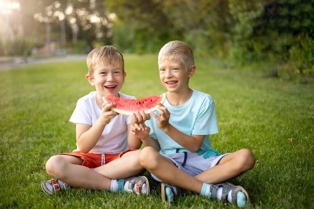 Dois meninos alegres e felizes comem melancia em uma clareira verde ensolarada com comida saudável e alegre