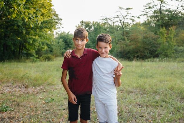 Dois meninos alegres estão parados no parque e sorrindo. infância feliz.