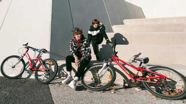 Dois meninos ao ar livre no parque com suas bicicletas