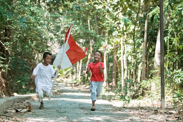 Dois meninos asiáticos correm segurando a bandeira vermelha e branca e levantando a bandeira
