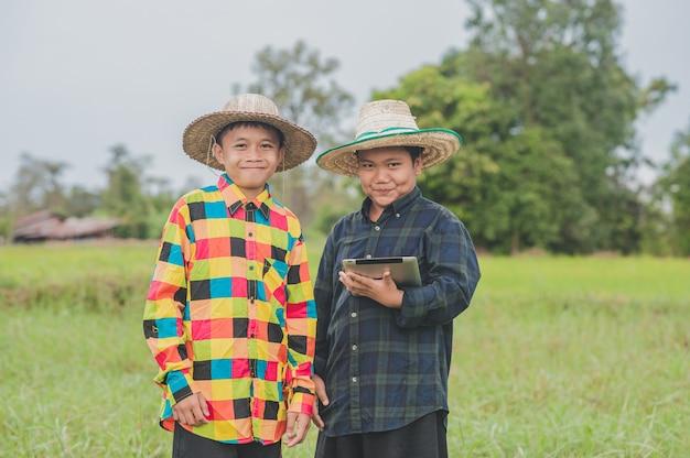 Dois meninos asiáticos usando tablet destacando-se fazendeiro da porta, fazendeiro inteligente de conceito ou escola de estudo de colagem de educação