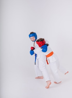 Dois meninos atletas em um quimono branco, capacete e luvas lutam em uma parede branca