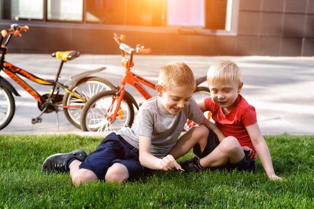Dois meninos brincam sentados na grama. descanse depois de pedalar, as bicicletas ao fundo Foto Premium