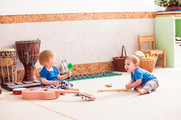 Dois meninos brincando com entusiasmo com vários instrumentos musicais