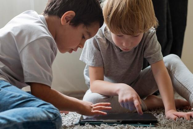 Dois meninos brincando com tablet em casa
