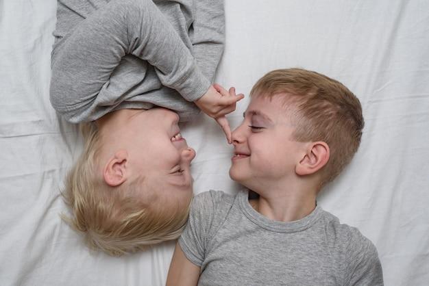 Dois meninos brincando deitada na cama. irmãos vista do topo