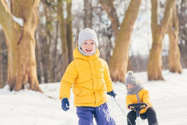 Dois meninos caminham juntos no parque de inverno e se divertem