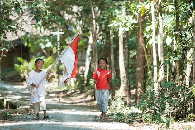 Dois meninos caminhando segurando a bandeira vermelha e branca e levantando a bandeira