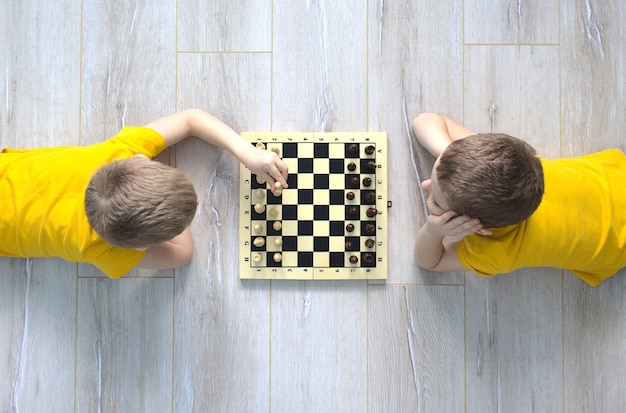 Dois meninos caucasianos jogando xadrez no chão