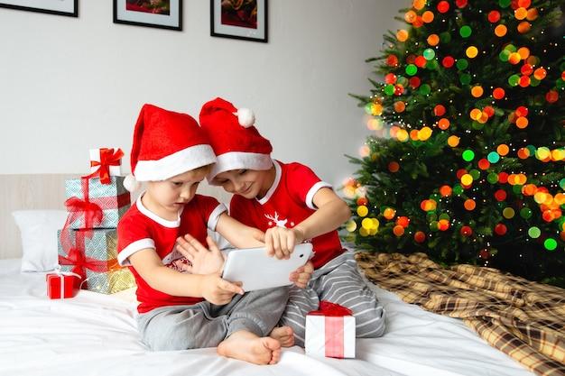 Dois meninos com chapéu de papai noel olhando para um tablet