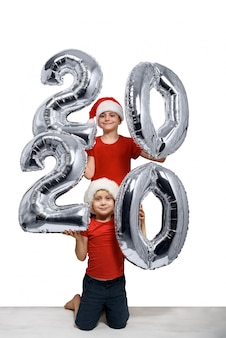 Dois meninos com chapéus de natal estão segurando a figura inflável prata 2020. ano novo