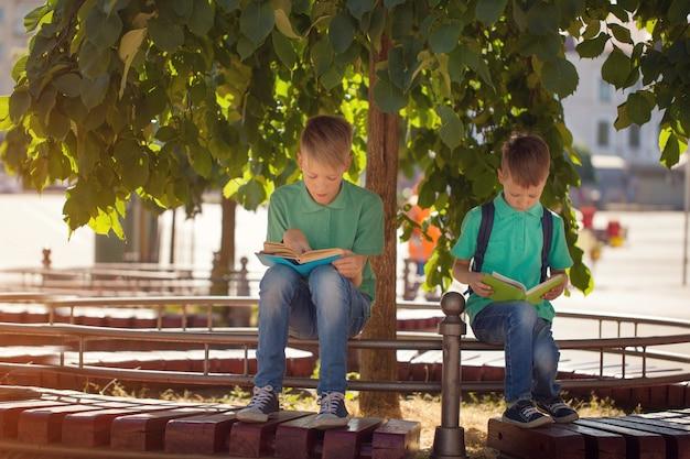 Dois meninos da escola sentado debaixo de uma árvore e ler livros em um dia ensolarado de verão