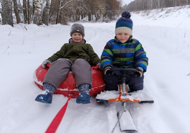 Dois meninos de aparência europeia vão alegremente de trenó e tubos na neve no dia de inverno