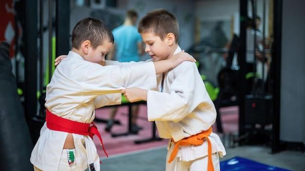 Dois meninos de quimono praticando artes marciais no ringue de uma academia