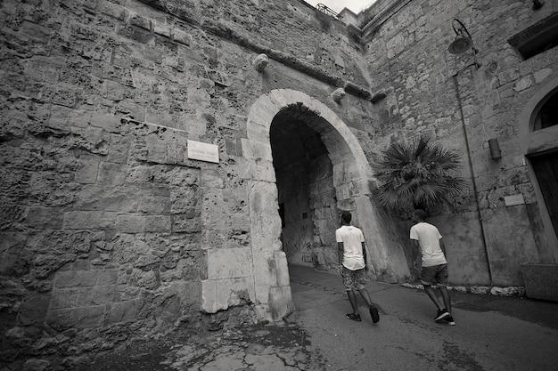 Dois meninos de trás estão prestes a entrar em uma antiga porta pertencente ao centro histórico de cagliari