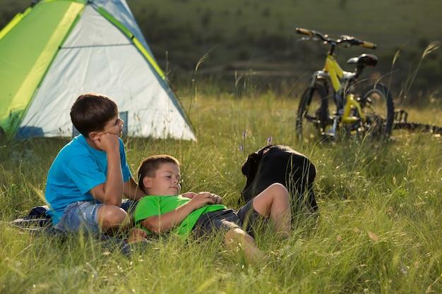 Dois meninos descansando deitados na grama com uma barraca e bicicletas ao fundo