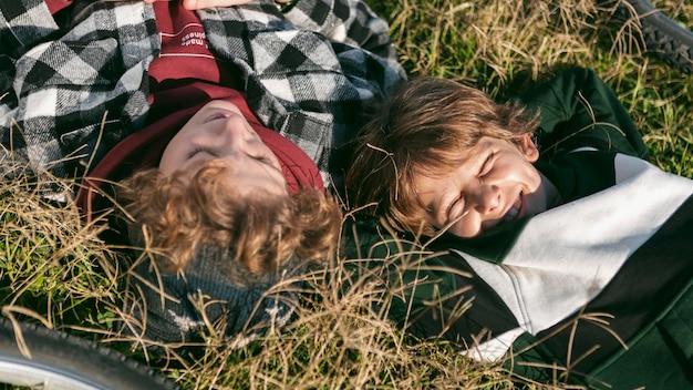 Dois meninos descansando na grama enquanto andam de bicicleta