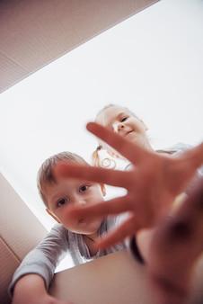 Dois meninos e meninas abrindo uma caixa de papelão e subindo no meio dela. as crianças se divertem