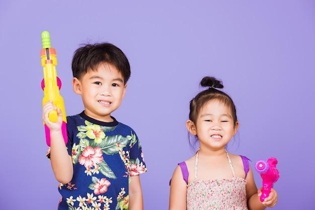 Dois meninos e meninas asiáticos segurando uma pistola d'água de plástico, dia do festival songkran na tailândia