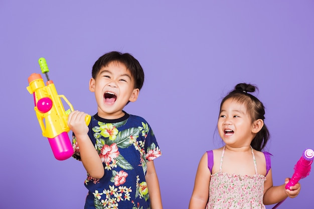 Dois meninos e uma menina felizes segurando um sorriso de pistola d'água de plástico para o festival songkran
