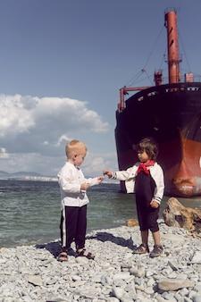 Dois meninos elegantes estão parados ao lado de um grande navio do rio que encalhou perto de novorossiysk