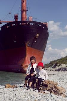 Dois meninos elegantes sentam-se ao lado de um grande navio do rio que encalhou perto de novorossiysk