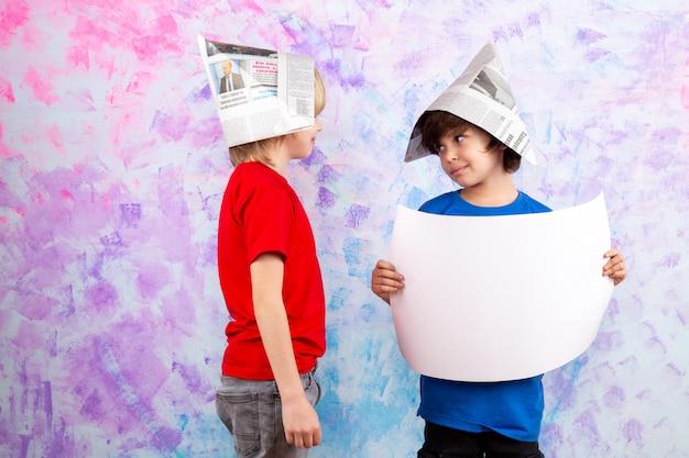 Dois meninos em camiseta vermelha e camiseta azul com chapéus de papel de parede na parede colorida