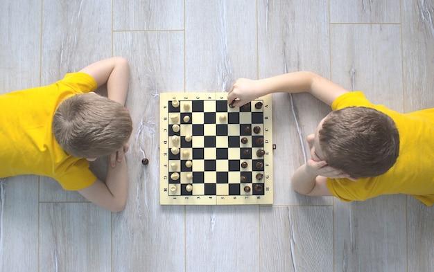 Dois meninos em camisetas amarelas estão jogando xadrez no chão