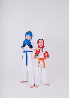 Dois meninos em quimonos brancos, capacete e luvas fazem uma pose em um fundo branco