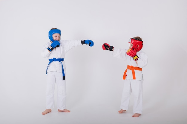 Dois meninos em um quimono branco e usando um capacete e luvas competem em uma parede branca