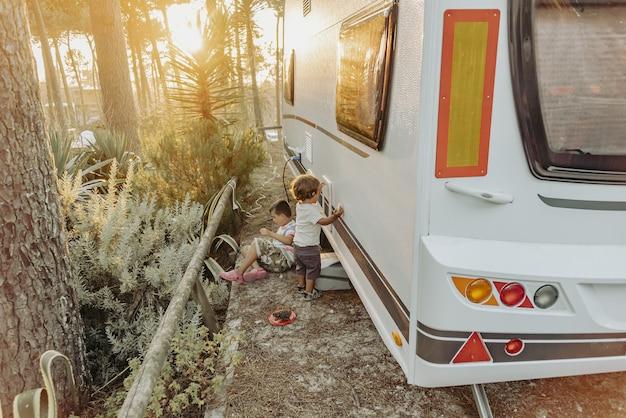 Dois meninos em uma caravana brincando na natureza
