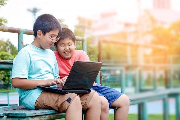 Dois meninos estão assistindo o computador no playground, sorrindo e rindo.
