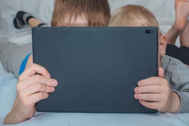 Dois meninos estão deitados na cama e olhando para o tablet