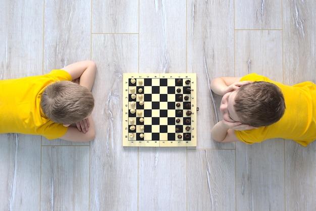 Dois meninos estão jogando xadrez no chão