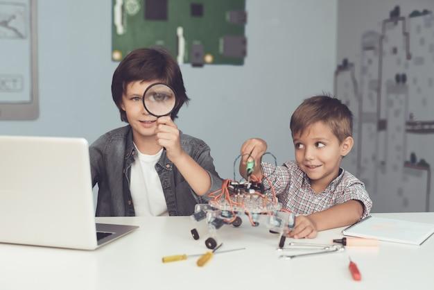 Dois meninos estão posando e olhando para a câmera.