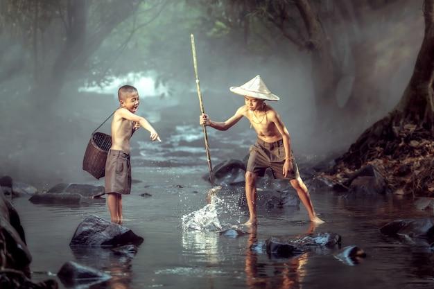 Dois meninos estão se divertindo alegremente. para pescar nos riachos. e este é o modo de vida das crianças no nordeste da tailândia.