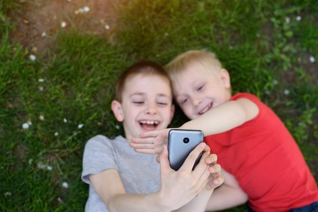 Dois meninos fazem selfie em um smartphone enquanto estava deitado na grama. vista do topo