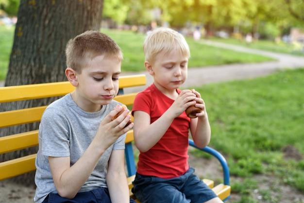 Dois meninos fazem um lanche em um banco no parque
