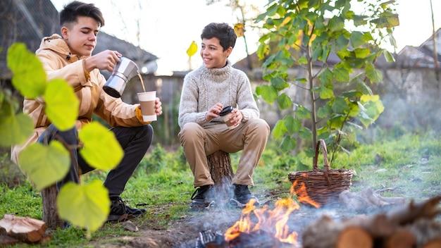 Dois meninos fazendo café em uma cafeteira em um piquenique, fogueira na frente deles