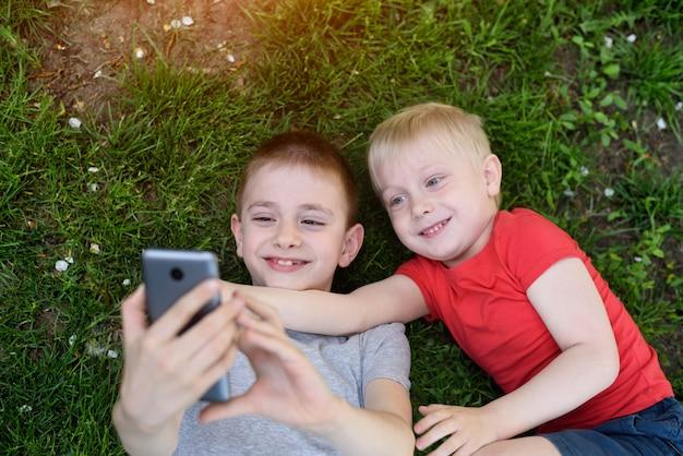 Dois meninos fazendo selfie em um smartphone deitados na grama