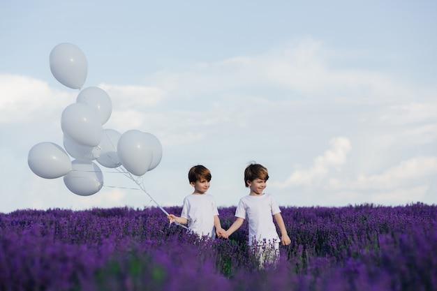 Dois meninos felizes de mãos dadas em um campo de lavanda
