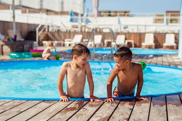 Dois meninos felizes felizes de 6-7 anos espirrando na piscina no verão de férias perto do hotel. caucasiano e asiático.
