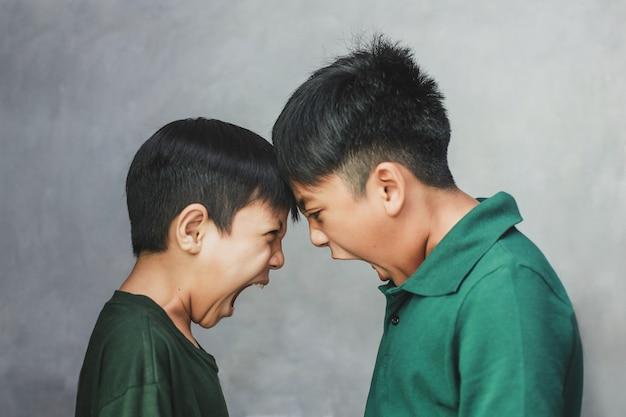 Dois meninos furiosos gritando um com o outro em um fundo cinza